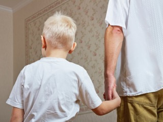 young blonde boy is led down the hall by his father
